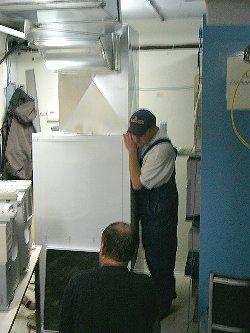 [Photo: Workmen installing new air conditioner]
